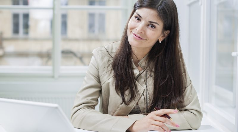 Portrait of confident businesswoman with laptop sitting at office desk